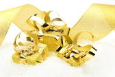Three golden christmas gifts with ribbon on snow — Stock Photo