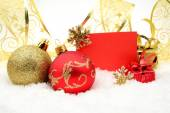 Golden and red christmas decoration on snow with wishes card — Stock Photo