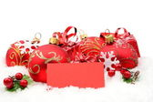 Red christmas decoration on snow with wishes card — Stock Photo
