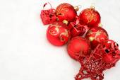 Group of red christmas baubles,gifts,star on snow at corner — Stock Photo
