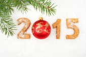 Date new year of 2015 homemade on snow with fir with red bauble — Stock Photo