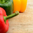 Closeup view of three coloured peppers on wooden plank — Stock Photo #62457851