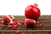 Studio shot open pomegranate on brown wooden mate — Stock Photo