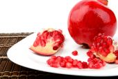Studio shot open pomegranate on plate wooden mate — Stock Photo
