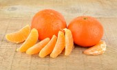 Mandarines with pieces isolated on wooden table — Stock Photo