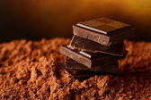 Heap of blocks of chocolate on cocoa powder — Stock Photo