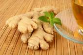 Ginger with tea-ingwertee on wooden mat — Stock Photo