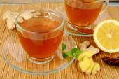 Ginger teas on wooden mat with lemon — Stock Photo