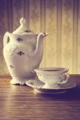 Old-fashioned vintage jug with tea with wallpaper background — Stock Photo