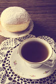 Doughnut with cup of tea in old-fashioned room on napkin — Stock Photo