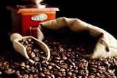 Overturned bag full of coffee beans on black with spatula and mill — Stock Photo