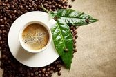Coffee with foam cup with beans on the left with green leaf on flax — Stock Photo