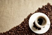 Frothy coffee cup with beans in the corner on fabric flax — Stock Photo