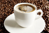 Macro shot of coffee cup with foam at breakfast — Stock Photo