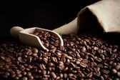 Overturned bag full of coffee beans on black with spatula — Stock Photo