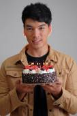 Asian man with birthday ice-cream cake on fire — Stock Photo