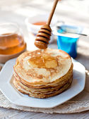 Pancakes with honey on the kitchen table — Photo
