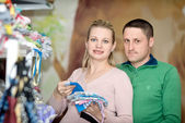 Pregnant woman buying baby clothes in supermarket  — Stockfoto
