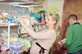 Pregnant woman buying baby clothes in supermarket  — Stock Photo