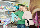 Pregnant woman buying baby clothes in supermarket  — Foto Stock