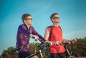 Two cyclists riding on a dirt road — Stockfoto