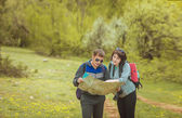 Tourists with a map in the forest — Stock Photo