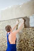 Laying Ceramic Tiles. Tiler placing ceramic wall tile in position over adhesive — Stock Photo