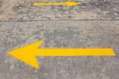 Yellow Traffic arrow on concrete road  — Stock Photo