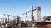 Building crane and construction site under blue sky — Stock Photo