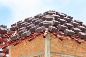 Roof under construction with stacks of roof tiles for home build — Stock Photo