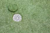 Artificial grass with drain water — Stock Photo