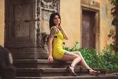 Una bella donna in un vestito giallo, tatuaggi, si siede sulla Maximus — Foto Stock