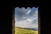 Cultivated hills through medieval window — Stock Photo