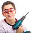 Child wearing red glasses and holding a cordless drill — Stock Photo #66097975