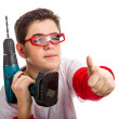 Child wearing red goggles and holding a cordless drill makes suc — Stock Photo #66098065
