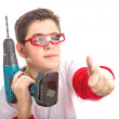 Child wearing red goggles and holding a cordless drill makes suc — Stock Photo #66098163