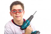 Child wearing red goggles and holding a cordless drill — Stock Photo