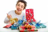 Happy boy makes success sign with thumb receiving Christmas gift — Стоковое фото