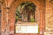 Italian cloister seen through an iron grate — Stock Photo