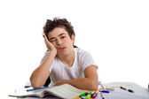Tired boy holds his face in front of homework  — Stock fotografie