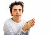 A boy is praying holding Rosary with both hands — 图库照片