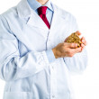 Doctor in white coat showing a wooden heart — Stock Photo #70535895