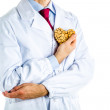 Doctor in white coat showing a wooden heart — Stock Photo #70535911
