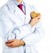 Doctor in white coat showing a wooden heart — Stock Photo #70536243