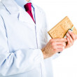 Doctor in white coat holding cork book and syringe — Stock Photo #70536989
