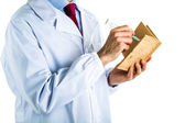 Doctor in white coat writing in cork book with syringe — Stockfoto