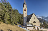 Church of St. Jacob overlooking pine forests and snow-capped pea — Stock Photo