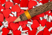 Pencil on heart shaped paper clip background. — Stock Photo