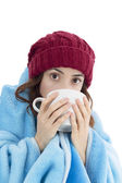 Woman warming herself under a blanket and with a cup of tea — Stock Photo