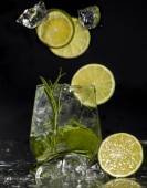 Gin and tonic cocktail with lime over black background. — Stock Photo